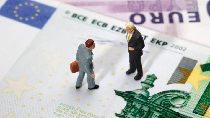 Muñequitos de un abogado y un cliente encima de billete de euro
