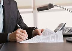 Una persona sentada en una mesa con unos papeles en las manos.