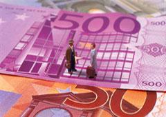 Dos muñequitos se dan la mano sobre billetes de euros