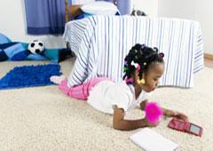 Una niña echada en el suelo jugando con la nintendo.