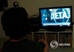 A woman watches a news program announcing the dissolution of armed Basque separatists ETA due for the first week of May, according to local television station ETB, in Guernica, April 18, 2018