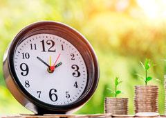 Reloj y dos montones de monedas de euro