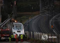 Varios trabajadores con la locomotora del tren que descarriló, el 28 de julio de 2013