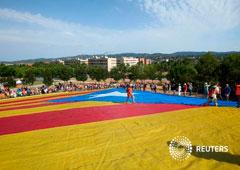 Varias personas sobre una gigantesca bandera independentista en Sant Cugat del Valles, cerca de Barcelona, el 8 de julio de 2017