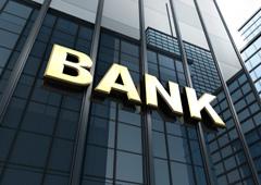 Un edificio formado con cuatro columnas y un tejado en tonos grises y la palabra 'BANK' en letras rojas