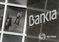 Los peatones se reflejan en el edificio de la sede Bankia en Madrid