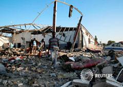 Los migrantes cargan los restos de sus pertenencias entre los escombros en un centro de internamiento de migrantes, golpeado por un ataque aéreo en el suburbio de Tajoura, en la capital libia de Trípoli, Libia, el 3 de julio de 2019