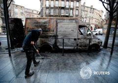 Un hombre barre la acera cerca de una furgoneta quemada durante una jornada nacional de protestas de los