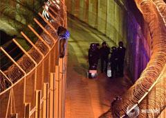 Un joven subsahariano permanece, ayer, encaramado a la valla fronteriza de Ceuta con Marruecos bajo la vigilancia de guardias civiles españoles