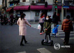 Una niña con una máscara monta un scooter en una calle del centro de Shanghái, China, el 23 de febrero de 2020.
