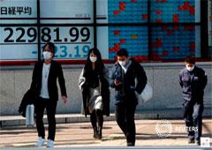 Personas con mascarillas pasan por delante de una pantalla que muestra el índice Nikkei en Tokio, Japón 3 de febrero de 2020.