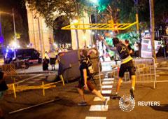 Imagen de los manifestandtes lanzando vallas contra la policía tras la manifestación celebrada el 1 de octubre en Barcelona, España
