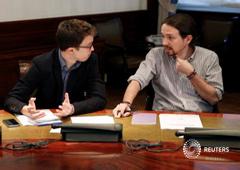 Iglesias habla con su compañero de partido Íñigo Errejón durante una reunión con los equipos negociadores de Cuidadanos, Podemos y el PSOE, en el Congreso en Madrid, el 7 de abril de 2016