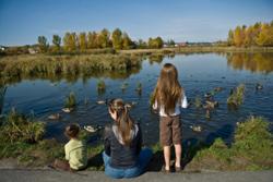Una madre en un parque natural con sus dos hijos.