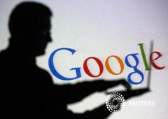 La silueta de una persona con un portátil delante de una pantalla con el logo de Google, en una foto tomada en Zenica el 29 de octubre de 2014