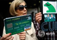 Una manifestante con un cartel que simula una tarjeta falsa de Caja Madrid