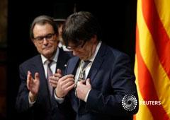 Carles Puigdemont mira una medalla recibida del anterior presidente catalán, Artur Mas (izquierda), durante la toma de posesión de Puigdemont como presidente de la Generalitat de Catalunya en el Palau de la Generalitat en Barcelona, 12 de enero de 2016