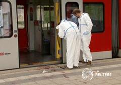 Investigadores de la policía miran huellas machadas de sangre fuera de un tren y en el anden tras un ataque con cuchillo en la estación de tren de Grafing, al sureste de Múnich, Alemania, en esta imagen extraída de un vídeo, el 10 de mayo de 2016