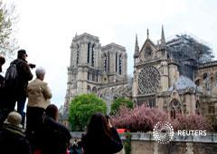 Transeúntes toman fotografías de la catedral de Notre-Dame en París después del incendio que destruyó partes de la estructura gótica. April 16, 2019