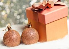 Dos bolas de navidad junto a una caja de regalo