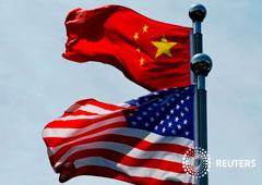 FOTO DE ARCHIVO: Las banderas de China y Estados Unidos ante un edificio del Estado chino en Shanghái.