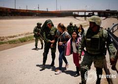 Miembros de la Guardia Nacional de México escoltan a una mujer de Nicaragua y a su hija luego de detenerlas cuando intentaban cruzar ilegalmente la frontera entre Estados Unidos y México, en Ciudad Juárez, México. 21 de junio, 2019.