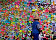 Un trabajador pasa por delante de unos post-it con mensajes pegados por los manifestantes en las paredes de la Asamblea Legislativa de Hong Kong, un día después de que irrumpieran en el edificio, en Hong Kong, China, el 2 de julio de 2019