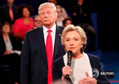 Trump escucha mientras Clinton responde una pregunta de la audiencia durante su debate en la Universidad de Washington en St. Louis, Missouri, el 9 de octubre de 2016