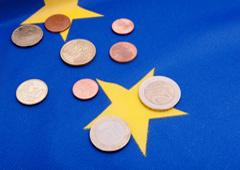 Bandera de la UE y monedas de euros