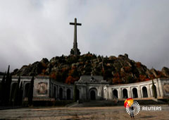 A woman holds an umbrella at the Valle de los Caidos (The Valley of the Fallen), the mausoleum holding the remains of former Spanish dictator Francisco Franco, on the 43rd anniversary of his death in San Lorenzo de El Escorial, outside Madrid, Spain, Nove
