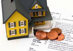 Maqueta de una casa con documentos y monedas