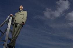 Un hombre subido a una escalera mirando al cielo