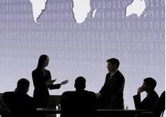 Un grupo hablando entre ellos en una mesa y de fondo una imagen con números binarios y parte del mapa mundi