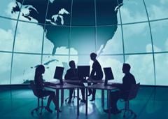 Personas reunidas alrededor de una mesa con el mapa del mundo de fondo