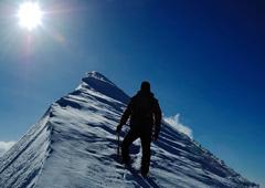 Persona escalando una montaña nevada