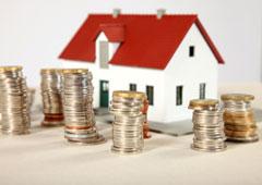 Casa y montoncitos de monedas