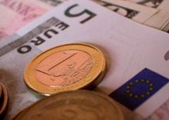 Un billete de 5 euros y una moneda de euro y otra de céntimo encima del billete