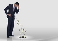 Hombre viendo cómo cae dinero por un agujero