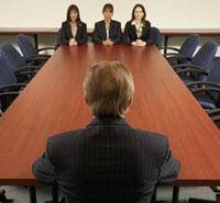 Jefe en un lado de una larga mesa con tres trabajadoras en la otra punta