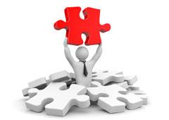 Un muñeco entre fichas de puzle levantando una ficha roja