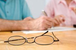Unas gafas sobre una mesa en la que dos personas están escribiendo sobre un papel