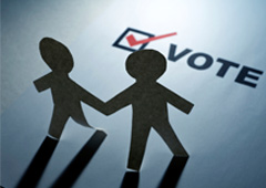 Dos muñecos de papel y una casilla de voto marcada