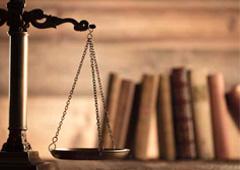 Una balanza de justicia con unos libros al fondo