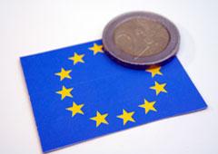 Bandera UE y una moneda de euro