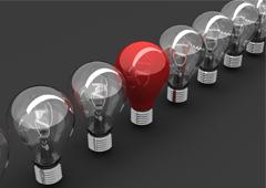 En un fondo gris una fila de bombillas y en medio de ellas una roja