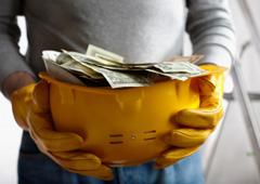 Persona sujetando un casco de obra con billetes dentro