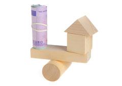 Casita de madera en equilibro con un rollo de billetes