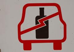 Dibujo de una botella dentro de un coche tachada