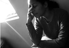 Persona sentada con síntomas de dolor