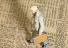 Figura de hombre con maletín andando encima de un periódico